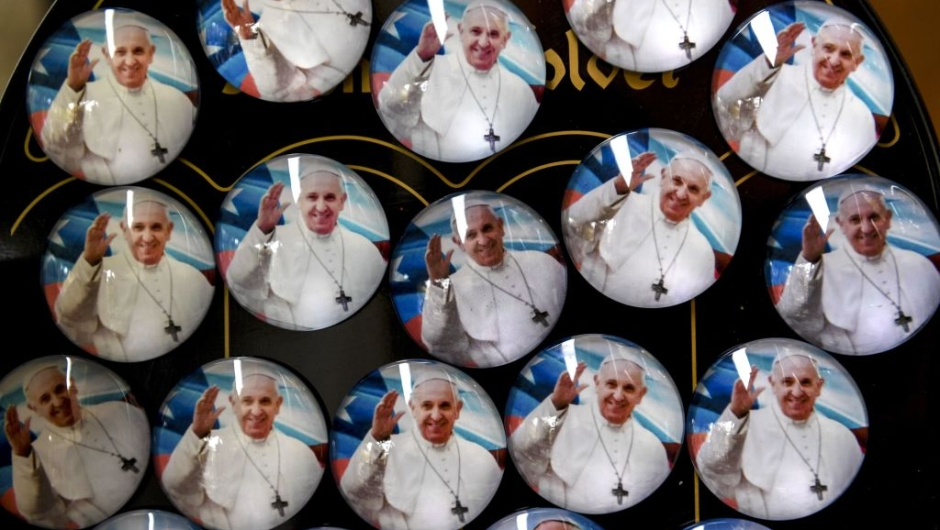 Pins of Pope Francis are sold at a street stall ahead of the pontiff's visit to Chile, in Santiago, on January 13, 2018. Pope Francis will be visiting Chile from January 15 to 18. / AFP PHOTO / Martin BERNETTI (Photo credit should read MARTIN BERNETTI/AFP/Getty Images)