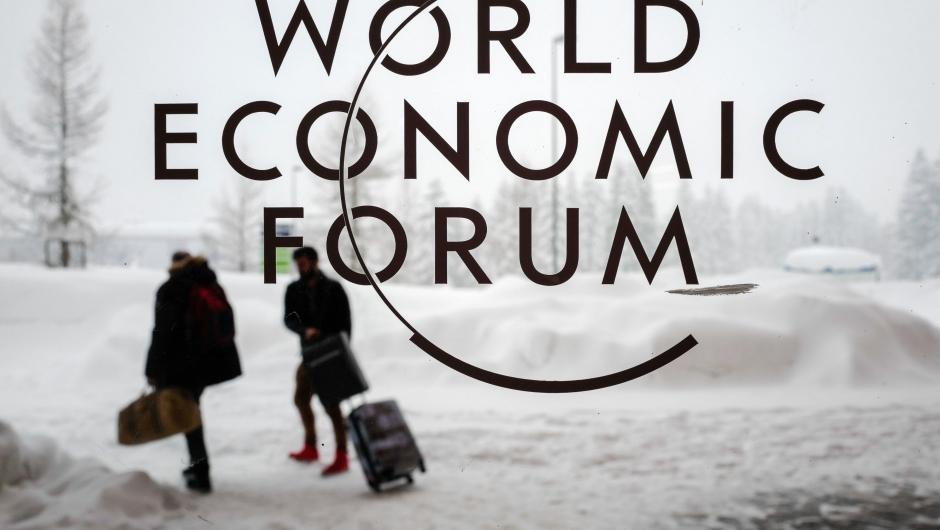 Two people leave the Congress Centre under snow ahead of the opening of the World Economic Forum (WEF) 2018 annual meeting, on January 22, 2018 in Davos, eastern Switzerland. US President Donald Trump's participation at the World Economic Forum in Davos, Switzerland next week could be thrown into question now that the federal government has partially shut down over budget wrangling, the White House said on January 20. / AFP PHOTO / Fabrice COFFRINI (Photo credit should read FABRICE COFFRINI/AFP/Getty Images)