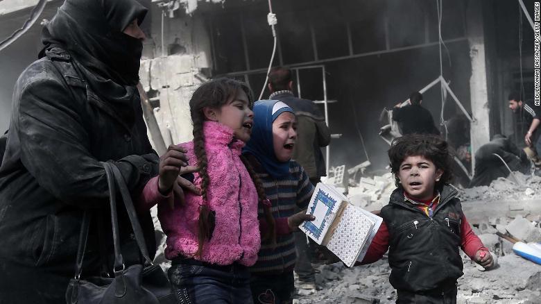 Una mujer y sus hijos corren para protegerse tras un bombardeo en Hamouria, el lunes 19 de febrero.