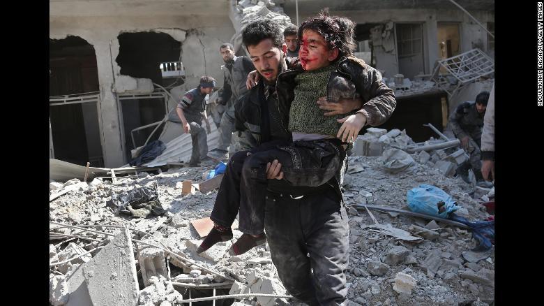 Bombardeo aéreo en Guta Oriental Un hombre rescata a un niño después de un bombardeo del régimen en la ciudad rebelde de Hamouria, en la asediada Guta Oriental, el miércoles 21 de febrero. Unas 300 personas murieron en tres días en los bombardeos en el enclave rebelde, dijeron médicos y activistas.