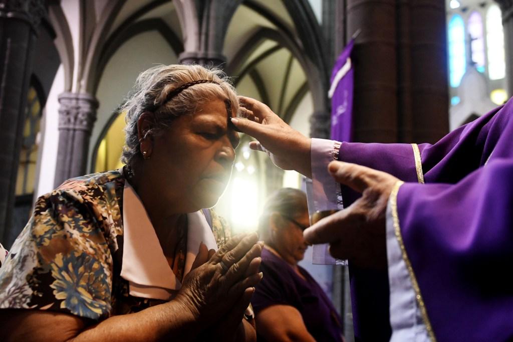 Una mujer recibe la señal de la cruz durante una misa el Miércoles de Ceniza en San Salvador. CRÉDITO: MARVIN RECINOS/AFP/Getty Images