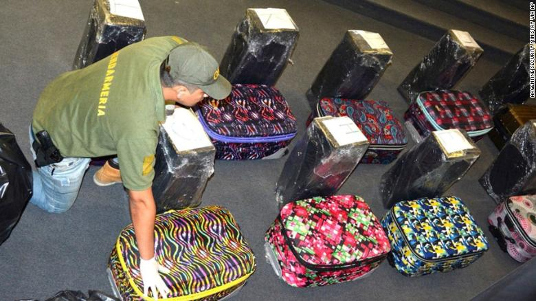 In this photo taken on Dec. 14, 2016, and released on Feb. 22, 2018, by the Argentine Security Ministry, a police officer guards suitcases that carried cocaine, that were found in an annex building of the Russian embassy in Buenos Aires, Argentina. A Russian diplomatic official and an Argentine police officer are among those arrested after authorities seized the cocaine shipment of 860 pounds (389 kilograms) at the Russian embassy in Buenos Aires that prompted them to launch a yearlong joint investigation to dismantle a drug ring, the government said. (Argentine Security Ministry via AP)