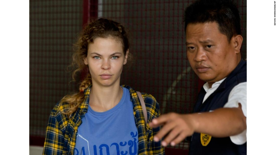 A police officer escorts Anastasia Vashukevich from a detention center in Pattaya, south of Bangkok, Thailand, Wednesday, Feb. 28, 2018, after she was arrested Sunday in the Thai resort city of Pattaya while giving sex lessons to Russian tourists. Vashukevich told The Associated Press from a police van Wednesday that she fears for her life, and wants to exchange information on alleged Russian ties to U.S. President Donald Trump???s campaign for her own personal safety. (AP Photo/Gemunu Amarasinghe)