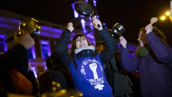 Women bang pots and pans as shooting slogans during a protest marking the beginning of a 24-hour women strike at the Sol square in Madrid, early Thursday, March 8, 2018. Women in Spain have been called for a 24-hour feminist strike in their workplaces and also stop doing duties at home during the International Women's Day. (AP Photo/Francisco Seco)