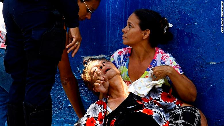 A woman is overcome by tear gas that was used to disperse the relatives of prisoners who were waiting to hear news about their family members imprisoned at a police station where a riot broke out, in Valencia, Venezuela, Wednesday, March 28, 2018. In a state police station housing more than one hundred prisoners, a riot culminated in a fire, requiring authorities to open a hole in a wall to rescue the inmates. (AP Photo/Juan Carlos Hernandez)