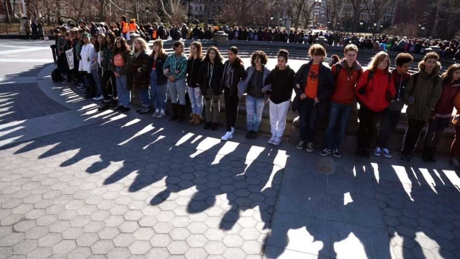Students from Harvest Collegiate High School form a circle around the fountain in Washington Square Park on March 14, 2018 in New York to take part in a national walkout to protest gun violence, one month after the shooting in Parkland, Florida, in which 17 people were killed. Students across the US walked out of classes on March 14, in a nationwide call for action against gun violence following the shooting deaths last month at a Florida high school. The nationwide protest is being held one month to the day after Nikolas Cruz, a troubled 19-year-old former student at Stoneman Douglas, unleashed a hail of gunfire on his former classmates. / AFP PHOTO / TIMOTHY A. CLARY (Photo credit should read TIMOTHY A. CLARY/AFP/Getty Images)