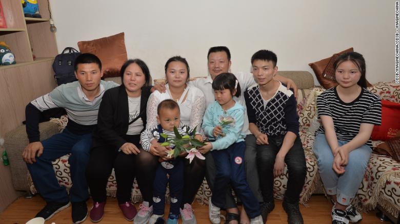 Las familias de Wang Mingqing y su hija desaparecida Kang Ying, segunda a la izquierda, posan para las fotos después de reunirse.
