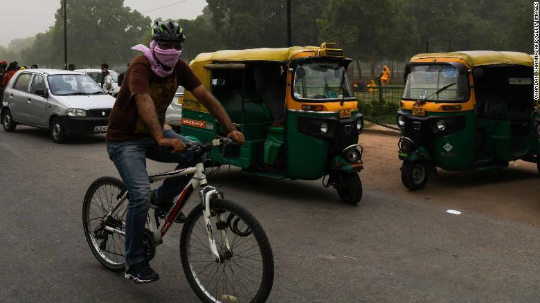 Un hombre se cubre la cara mientras va en bicicleta durante una tormenta de polvo en Nueva Delhi, el 2 de mayo. (Crédito: CHANDAN KHANNA/AFP/Getty Images)