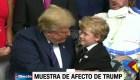 Un niño intenta abrazar a un distraído Trump