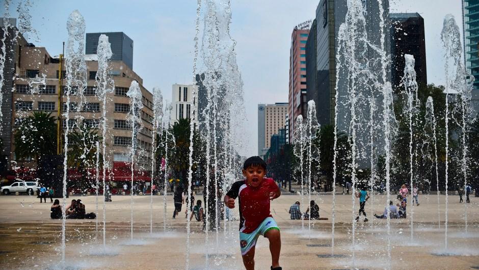 Niño salta en una fuente en Ciudad de México. (Crédito: RONALDO SCHEMIDT/AFP/Getty Images)