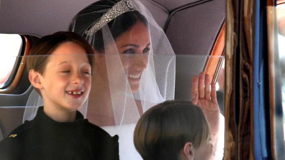 Los niños John y Brian Mulroney, pajes de Meghan Markle, con ella en el coche mientras saluda a su llegada. (Crédito: CHRIS RADBURN/AFP/Getty Images)