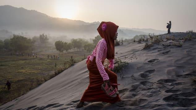 """Una mujer musulmana camina sobre el """"mar de arenas"""" mientras se prepara para la oración en la playa Parangkusumo en Yogyakarta, Indonesia."""