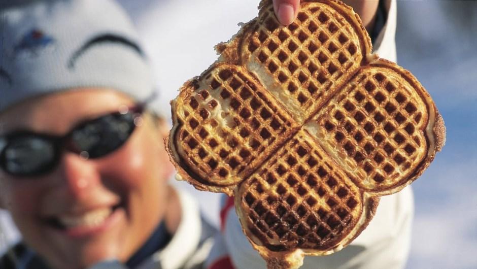 Los waffles blandos noruegos con forma de corazón a menudo se comen con brunost, un queso de cabra hecho de suero de leche caramelizado, con un sabor de dulce de leche afrutado y sabor dulce.