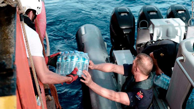 Un funcionario de la marina de Malta reparte agua al barco de rescate. (Crédito: Kenny Karpov/SOS Mediterranee via AP)