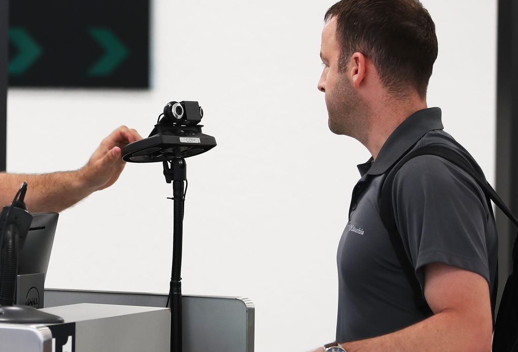 MIAMI, FL - FEBRUARY 27: A U.S. Customs and Border Protection officer instructs an international traveler to look into a camera as he uses facial recognition technology to screen a traveler entering the United States on February 27, 2018 at Miami International Airport in Miami, Florida. The facility is the first in the country that is dedicated to providing expedited passport screening via facial recognition technology, which verifies a traveler's identity by matching them to the document they are presenting. (Photo by Joe Raedle/Getty Images)
