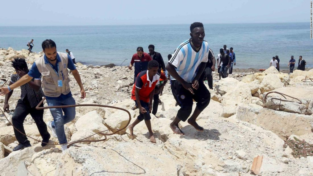 Los migrantes que sobrevivieron al hundimiento escalan la costa rocosa de al-Hmidiya, al este de la capital, Trípoli. (Crédito: MAHMUD TURKIA/AFP/Getty Images)