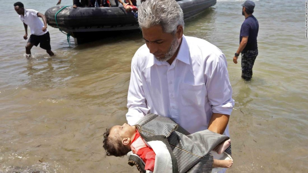 Un hombre lleva el cuerpo de uno de los tres bebés muertos en el Mediterráneo. (Crédito: MAHMUD TURKIA/AFP/Getty Images)