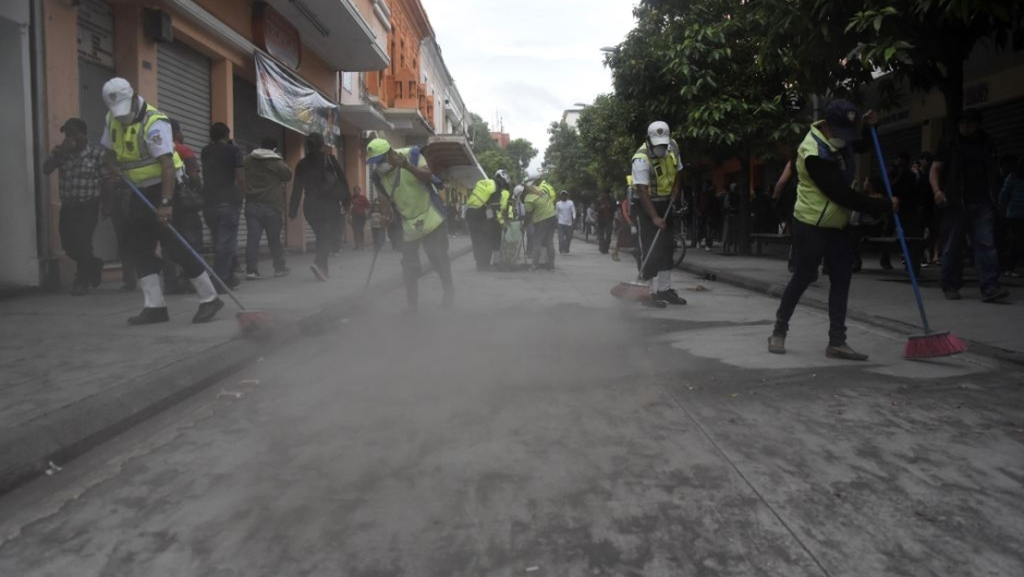 Municipal employees sweep up ash after the eruption of the Fuego Volcano, in Guatemala City, on June 3, 2018. (Photo by JOHAN ORDONEZ / AFP) (Photo credit should read JOHAN ORDONEZ/AFP/Getty Images)