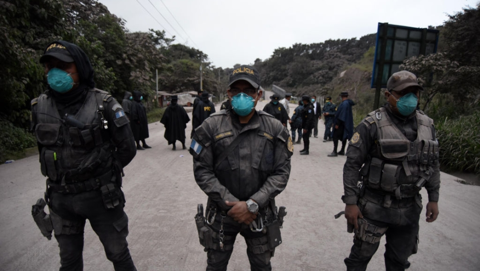 TOPSHOT - Police officers are posted in Alotenango municipality, Sacatepequez department, about 65 km southwest of Guatemala City, as the Fuego Volcano erupts on June 3, 2015. (Photo by ORLANDO ESTRADA / AFP) (Photo credit should read ORLANDO ESTRADA/AFP/Getty Images)