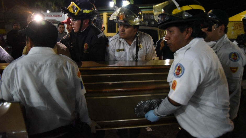 Volunteer firefighters carry a coffin with the body of Sergio Vasquez who died following the eruption of Fuego volcano on June 3, to a morgue in Alotenango municipality, Sacatepequez, about 65 km southwest of Guatemala City, on June 4, 2018. - Emergency workers will resume the search on June 4 for Guatemalans missing after the eruption of the Fuego volcano, which belched out clouds of ash and flows of lava and left at least 25 people dead. (Photo by ORLANDO ESTRADA / AFP) (Photo credit should read ORLANDO ESTRADA/AFP/Getty Images)