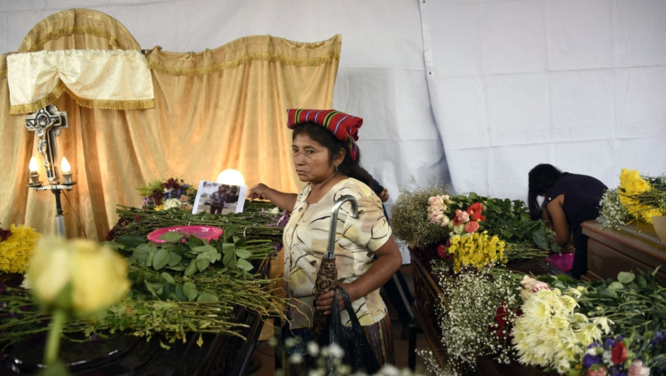 A woman attends the wake of seven victims who died following the eruption of the Fuego volcano, at the morgue in Alotenango municipality, Sacatepequez, about 65 km southwest of Guatemala City, on June 4, 2018. - Rescue workers Monday pulled more bodies from under the dust and rubble left by an explosive eruption of Guatemala's Fuego volcano, bringing the death toll to at least 62. (Photo by JOHAN ORDONEZ / AFP) (Photo credit should read JOHAN ORDONEZ/AFP/Getty Images)