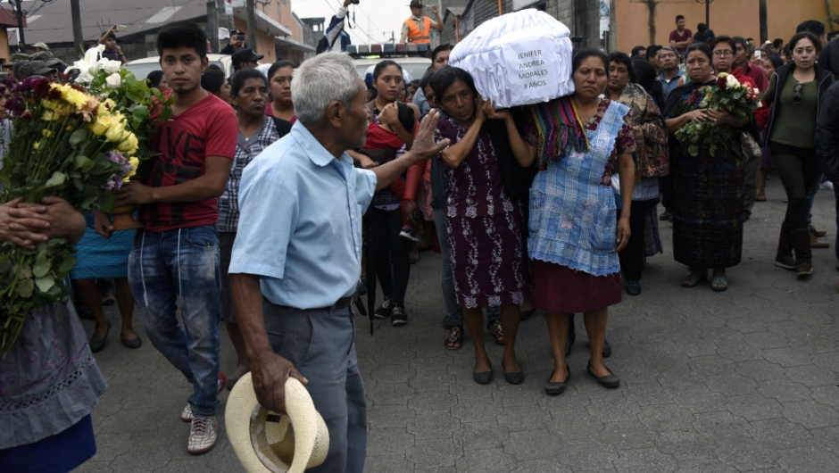 TOPSHOT - Two women carry the coffin of a little girl who died, following the eruption of the Fuego volcano, along the streets of Alotenango municipality, Sacatepequez, about 65 km southwest of Guatemala City, on June 4, 2018. - Rescue workers Monday pulled more bodies from under the dust and rubble left by an explosive eruption of Guatemala's Fuego volcano, bringing the death toll to at least 62. (Photo by JOHAN ORDONEZ / AFP) (Photo credit should read JOHAN ORDONEZ/AFP/Getty Images)