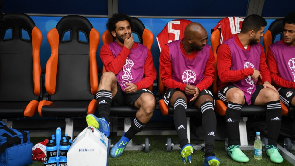 YEKATERINBURG, RUSSIA - JUNE 15: Mohamed Salah of Egypt looks on from the bench during the natonal anthems prior to the 2018 FIFA World Cup Russia group A match between Egypt and Uruguay at Ekaterinburg Arena on June 15, 2018 in Yekaterinburg, Russia. (Photo by Matthias Hangst/Getty Images)