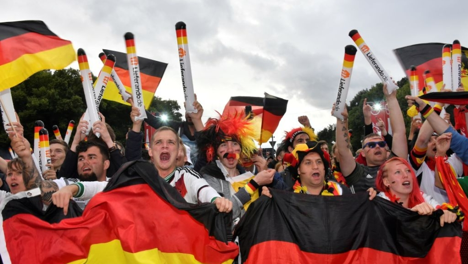 Supporters of the German national football team wave national flags as they watch on a giant screen the Russia 2018 World Cup Group F football match between Germany and Sweden on June 23, 2018 in Berlin. (Photo by John MACDOUGALL / AFP) (Photo credit should read JOHN MACDOUGALL/AFP/Getty Images)