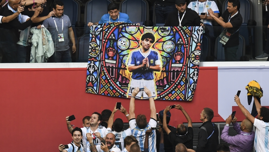 Diego Maradona asiste al encuentro entre Argentina y Nigeria con un póster de sí mismo dibujado como un santo. (Crédito: PAUL ELLIS/AFP/Getty Images)