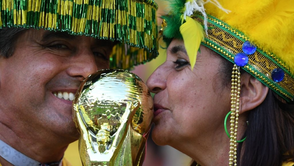 Brazilian fans kiss a replica of the FIFA World Cup trophy before the Russia 2018 World Cup Group E football match between Serbia and Brazil at the Spartak Stadium in Moscow on June 27, 2018. (Photo by Kirill KUDRYAVTSEV / AFP) / RESTRICTED TO EDITORIAL USE - NO MOBILE PUSH ALERTS/DOWNLOADS (Photo credit should read KIRILL KUDRYAVTSEV/AFP/Getty Images)