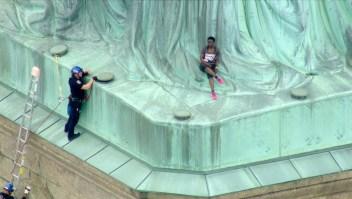 Una mujer trepa la Estatua de la Libertad