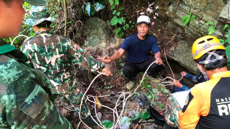Expertos voluntarios de montañismo se preparan para descender a una abertura en la roca para investigar si hay una ruta hacia la cueva donde están los niños. Están acompañados por trabajadores de la autoridad del Parque Nacional y soldados tailandeses.