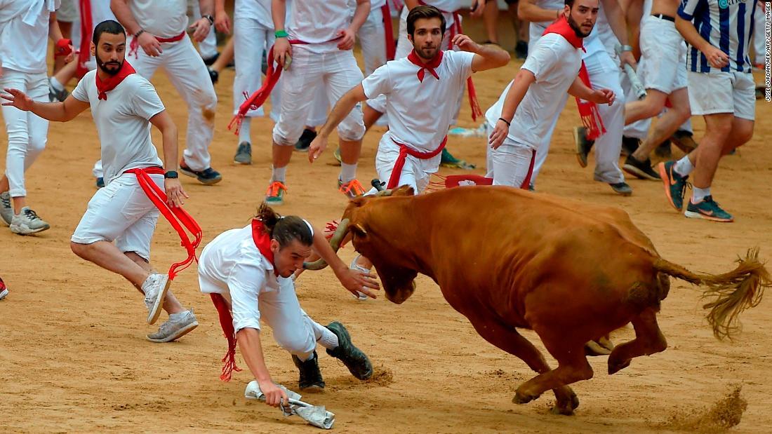 Los aficionados corren delante de los toros con trajes blancos y pañuelos rojos, según marca la tradición. (Crédito: JOSE JORDAN/AFP/Getty Images)