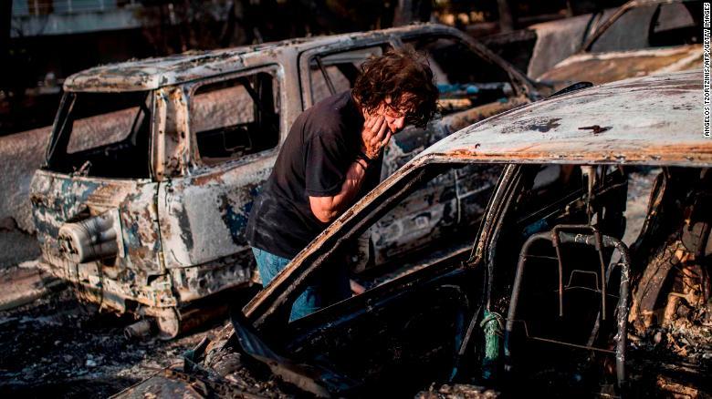 Una mujer busca a su perro después del incendio en Mati, cerca de la capital griega, Atenas. (Crédito: ANGELOS TZORTZINIS/AFP/Getty Images)
