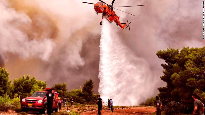 Un helicóptero de lucha contra incendios arroja agua para extinguir las llamas durante un incendio forestal en el pueblo de Kineta el martes.