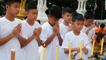 Chanin Vibulrungruang light a candle with members of the rescued soccer team attend a Buddhist ceremony that is believed to extend the lives of its attendees as well as ridding them of dangers and misfortunes in Mae Sai district, Chiang Rai province, northern Thailand, Tuesday, July 24, 2018. Eleven of the boys and their coach rescued last week from the flooded Tham Luang cave attend a merit making ceremony at a buddhist temple. The boys are also expected to have their heads shaved in the afternoon in preparation for their ordination as buddhist novices. (AP Photo/Sakchai Lalit)