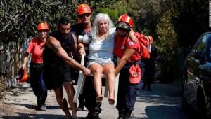 Miembros de los equipos de rescate llevan a una mujer herida en los incendios de Mati, en Grecia. (Crédito: AP Photo/Thanassis Stavrakis)