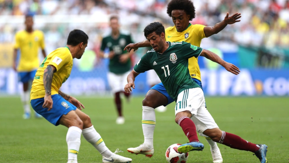 Carlos Vela of Mexico is challenged by Willian and Fagner of Brazil during the 2018 FIFA World Cup Russia Round of 16 match between Brazil and Mexico at Samara Arena on July 2, 2018 in Samara, Russia. (Photo by Buda Mendes/Getty Images)