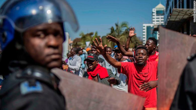La policía patrulla fuera de las oficinas de la Comisión Electoral de Zimbabwe mientras los partidarios de la oposición se reúnen en Harare. (Crédito: AP Photo/Mujahid Safodien)