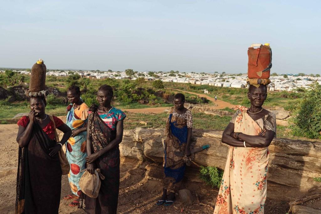 Las mujeres de Sudán del Sur esperan que otras se unan en el camino hacia el bosque para obtener leña. (Crédito: Hannah Reyes Morales)