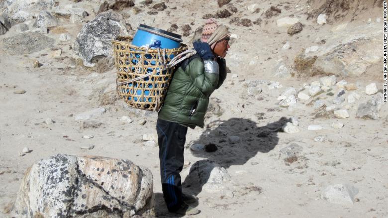Un porteador en el Everest, que se enfrenta a un problema por acumulación de desechos humanos.
