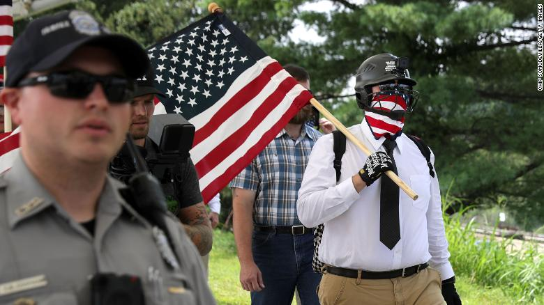 """VIENNA, VA - AUGUST 12:  Fairfax County Police escort white supremacists as they walk toward the Vienna/Fairfax GMU Metro Station to travel by train to the White House for the Unite the Right rally August 12, 2018 in Vienna, Virginia. Thousands of protesters are expected to demonstrate against the """"white civil rights"""" rally in Washington, which was planned by the organizer of last year's deadly rally in Charlottesville, Virginia.  (Photo by Chip Somodevilla/Getty Images)"""