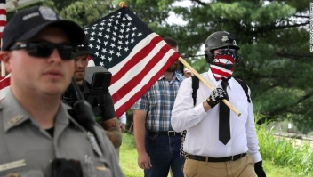 "VIENNA, VA - AUGUST 12: Fairfax County Police escort white supremacists as they walk toward the Vienna/Fairfax GMU Metro Station to travel by train to the White House for the Unite the Right rally August 12, 2018 in Vienna, Virginia. Thousands of protesters are expected to demonstrate against the ""white civil rights"" rally in Washington, which was planned by the organizer of last year's deadly rally in Charlottesville, Virginia. (Photo by Chip Somodevilla/Getty Images)"
