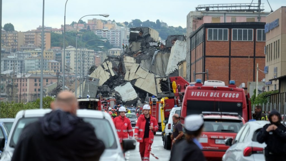 "TOPSHOT - A picture taken on August 14, 2018 in Genoa shows a section of a giant motorway bridge that collapsed earlier injuring several people. - Rescuers scouring through the wreckage after part of a viaduct of the A10 freeway collapsed said there were ""tens of victims"", while images from the scene showed an entire carriageway plunged on to railway lines below. (Photo by ANDREA LEONI / AFP) (Photo credit should read ANDREA LEONI/AFP/Getty Images)"