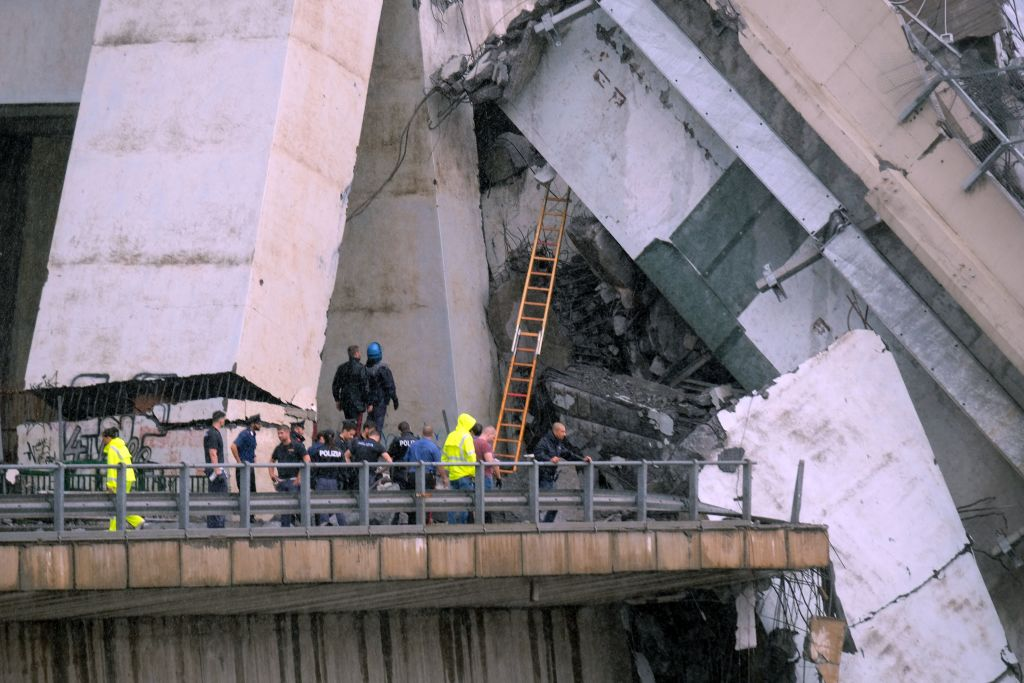 "Rescuers are at work amid the rubble of a section of a giant motorway bridge that collapsed earlier, on August 14, 2018 in Genoa. - Rescuers scouring through the wreckage after part of a viaduct of the A10 freeway collapsed said there were ""tens of victims"", while images from the scene showed an entire carriageway plunged on to railway lines below. (Photo by ANDREA LEONI / AFP) (Photo credit should read ANDREA LEONI/AFP/Getty Images)"