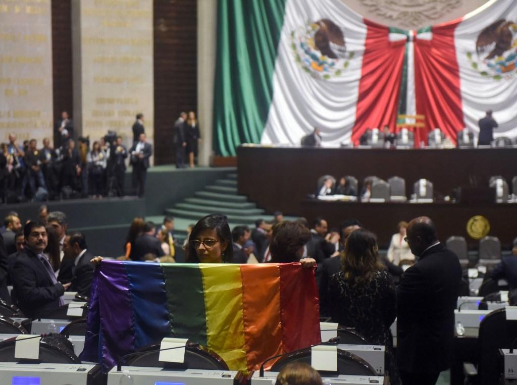 La diputada independiente Lucía Rioja posa con una bandera del arcoíris durante la inauguración de la legislatura LXIV en el Congreso en la Ciudad de México, el 29 de agosto de 2018. (Crédito: RODRIGO ARANGUA/AFP/Getty Images)