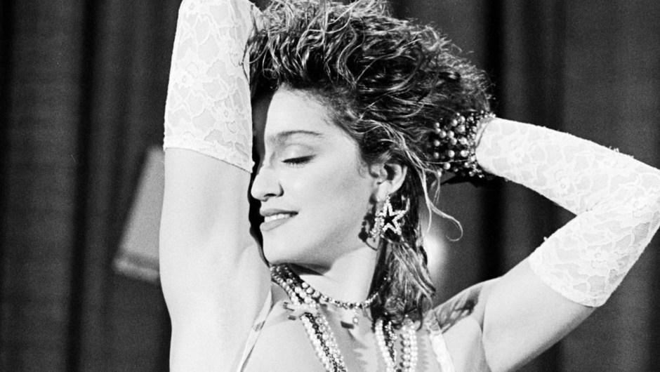 """¿En qué momento Madonna se convirtió en una mega estrella de la música y el estilo de primer orden? Su debut en vivo de """"Like a Virgin"""" en el primer VMA de MTV en 1984, cuando mejoró su estética dance-punk en el centro con encaje blanco y un crucifijo aún más grande. """"La nuestra era una familia estricta, pasada de moda"""", le dijo a People en 1985. """"Cuando era pequeña, mi abuela solía suplicarme que no fuera con hombres, que amara a Jesús y que fuera una buena chica. Crecí con dos imágenes de una mujer: la virgen y la puta. Fue un poco aterrador""""."""