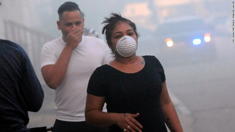 Los residentes se cubren la cara para protegerse del humo mientras evacuaban el jueves en Lawrence, Massachusetts.