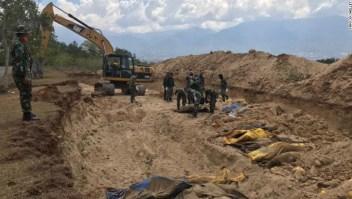 Funcionarios preparan una fosa común para enterrar cientos de muertos, algunos sin identificar.