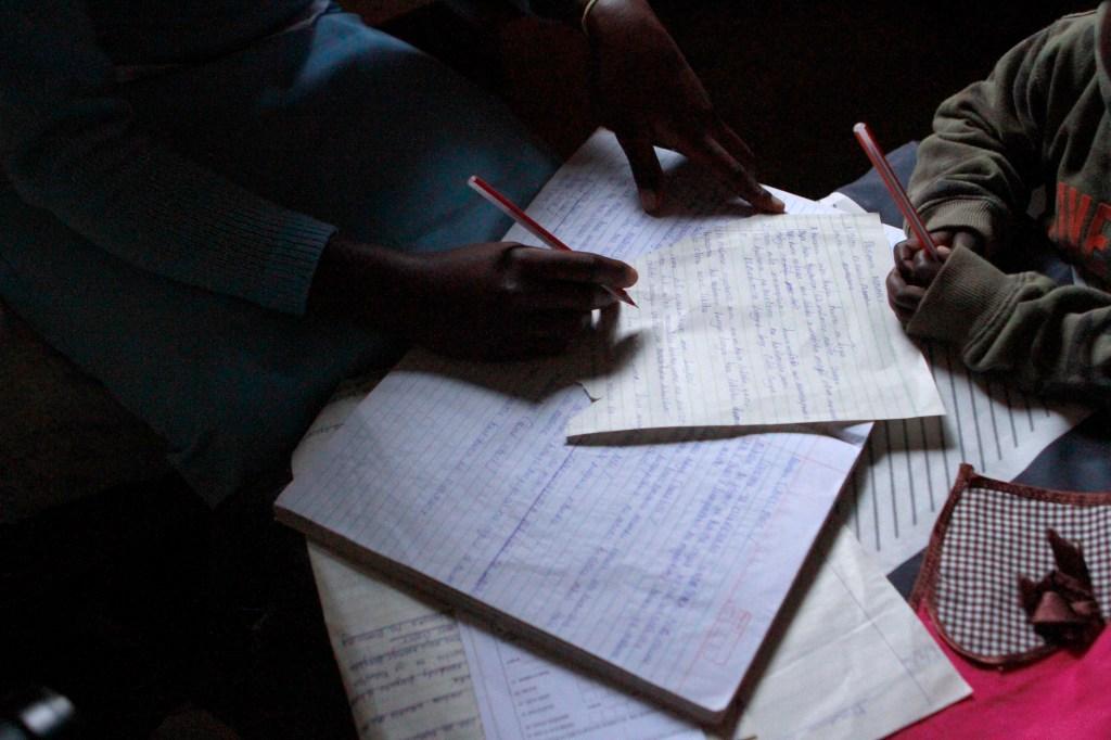 El hijo de Elifuraha mira, lápiz en mano, mientras ella hojea sus notas de una clase de sastrería en el Centro Faraja.